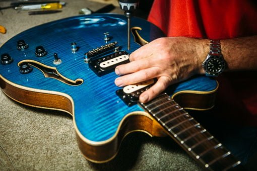 Chris Melville, guitar repairer in Brisbane, working on a guitar's pickups